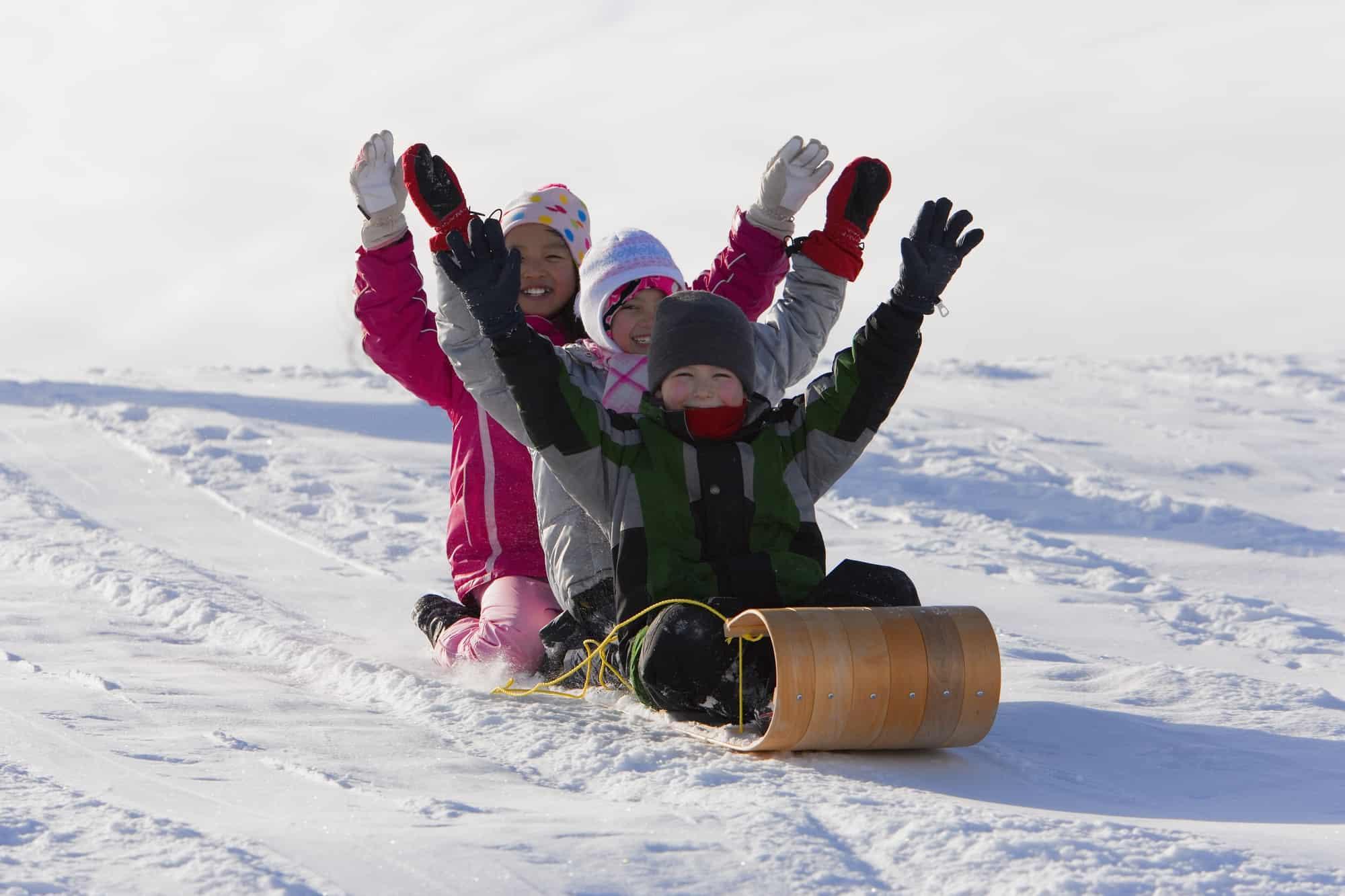 Happy kids tobogganing