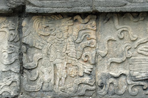 Stone carvings visible on stone buildings at Chichen Itza