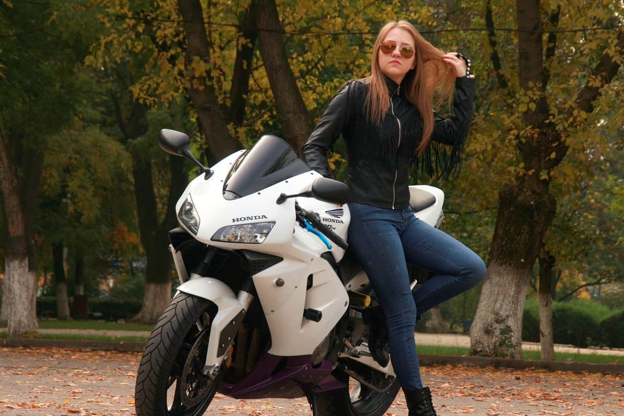 Woman wearing biker clothing standing beside a motorcycle