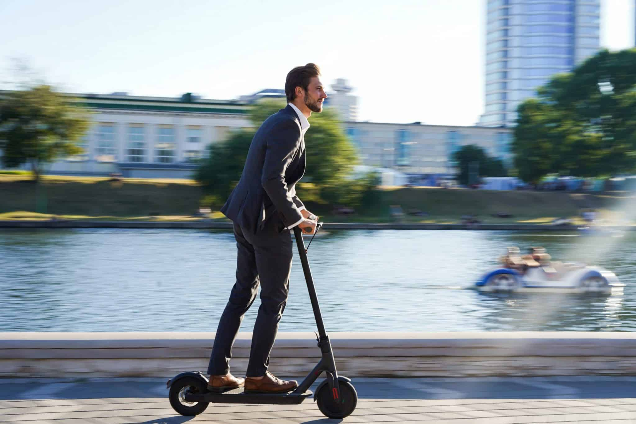 Man in business suit riding an e-scooter in Paris