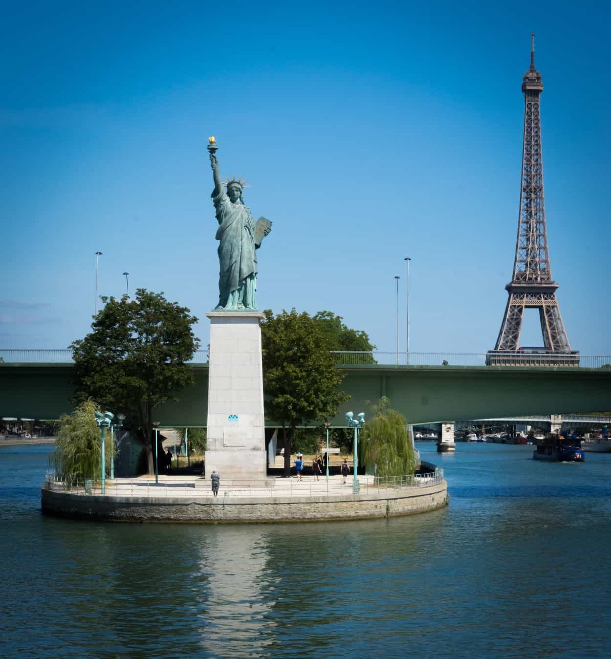 Statue of Liberty replica with Eiffel Tower in the background